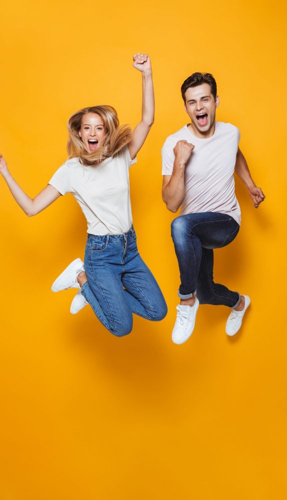 Photo,Of,Happy,Excited,Young,Loving,Couple,Jumping,Isolated,Over