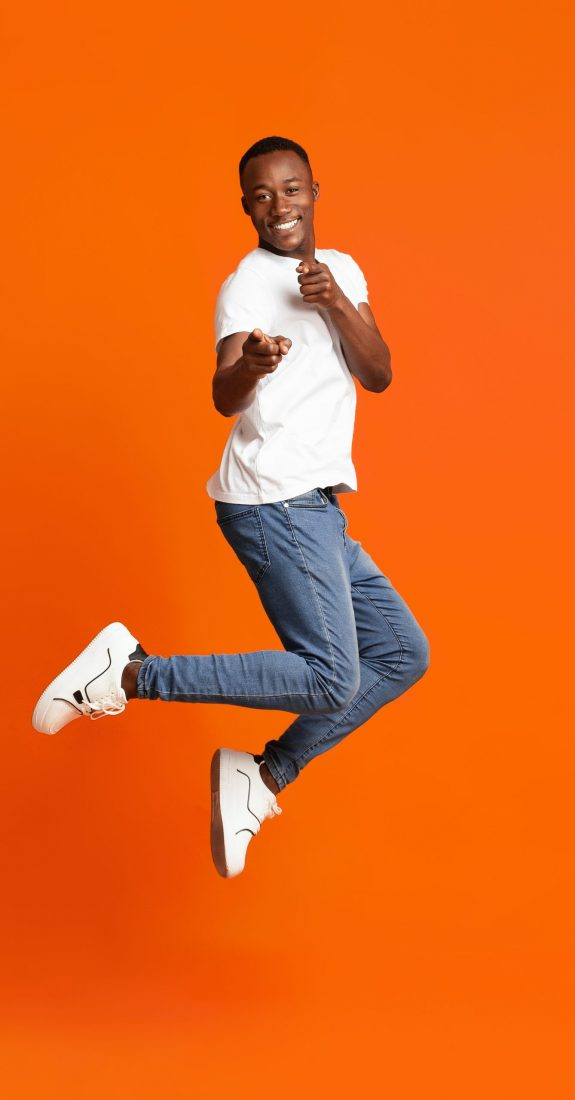 Charismatic,Black,Guy,Pointing,At,Camera,While,Jumping,Up,On